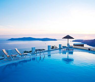Infinity pool in front of the ocean with sunbeds